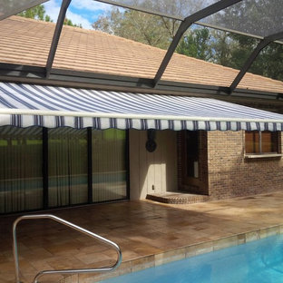 Photo of a back patio in Tampa with a water feature, tiled flooring and an awning.