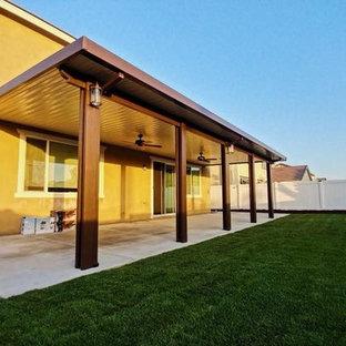Immagine di un grande patio o portico chic dietro casa con lastre di cemento e un gazebo o capanno