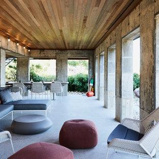Immagine di un patio o portico industriale dietro casa con un tetto a sbalzo e lastre di cemento
