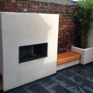 Ispirazione per un piccolo patio o portico chic in cortile con un focolare e graniglia di granito