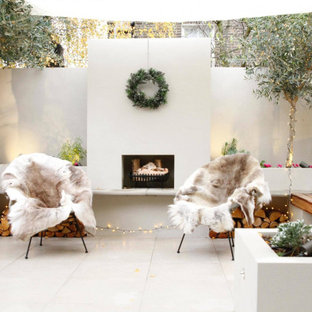 Photo of a contemporary back patio in London with a fireplace, tiled flooring and no cover.