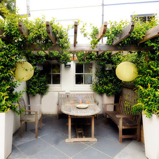 Example of a small tuscan backyard stone patio design in London with a pergola