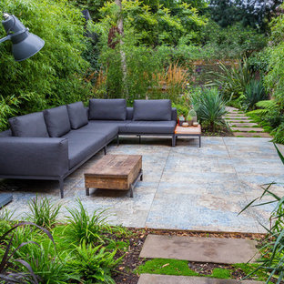 Large contemporary back patio in London with concrete paving and no cover.