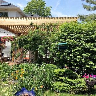 Ispirazione per un patio o portico stile americano di medie dimensioni e dietro casa con pavimentazioni in pietra naturale e una pergola