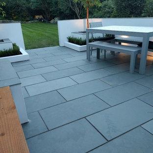 Ispirazione per un patio o portico contemporaneo di medie dimensioni e nel cortile laterale con pavimentazioni in pietra naturale