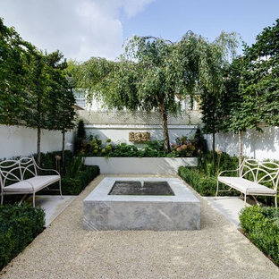This is an example of a small contemporary back patio in London with a water feature, gravel and no cover.