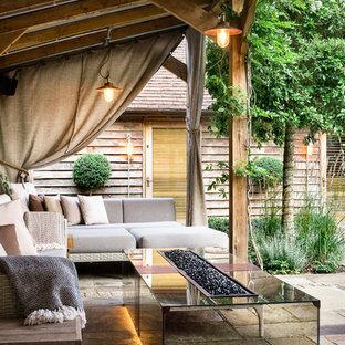 Foto di un grande patio o portico minimal in cortile con pavimentazioni in pietra naturale e un focolare