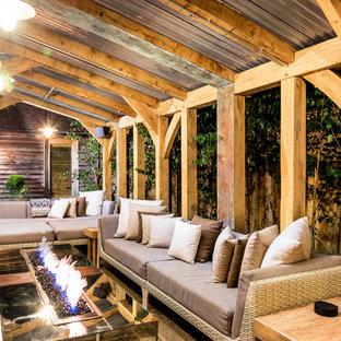 Idee per un grande patio o portico contemporaneo in cortile con pavimentazioni in pietra naturale e un focolare