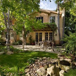 Ispirazione per un patio o portico boho chic dietro casa con fontane, pavimentazioni in cemento e una pergola