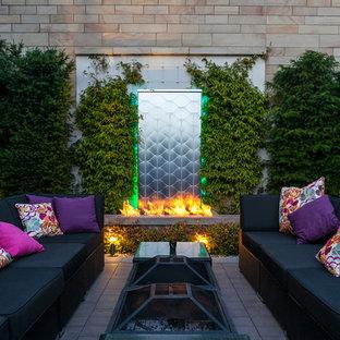 Idee per un patio o portico eclettico con un caminetto