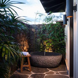 Idée de décoration pour une terrasse avec une douche extérieure ethnique de taille moyenne avec des pavés en pierre naturelle et une extension de toiture.