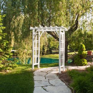 Ispirazione per un grande patio o portico etnico dietro casa con una pergola, fontane e pavimentazioni in pietra naturale