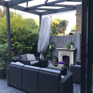 Immagine di un piccolo patio o portico stile shabby dietro casa con pedane e una pergola
