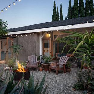 Foto di un piccolo patio o portico stile marinaro dietro casa con un giardino in vaso, ghiaia e un tetto a sbalzo