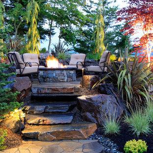 Ispirazione per un patio o portico eclettico con un focolare