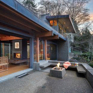 Foto di un grande patio o portico etnico davanti casa con un focolare, lastre di cemento e un tetto a sbalzo