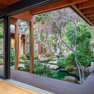 This is an example of a large world-inspired back patio in Other with a water feature, decking and an awning.