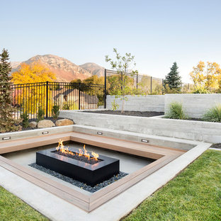 Example of a trendy concrete patio design in Salt Lake City with a fire pit and no cover