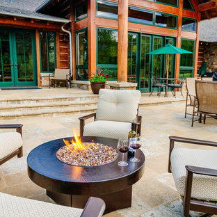 Patio - large rustic backyard tile patio idea in Denver with a fire pit and a roof extension