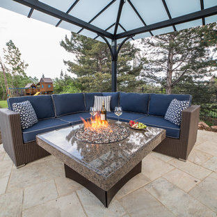 Inspiration for a mid-sized modern backyard stone patio remodel in Denver with a fire pit and a gazebo