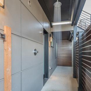 Ispirazione per un patio o portico minimal di medie dimensioni con lastre di cemento e un tetto a sbalzo