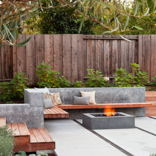 Cette photo montre une terrasse arrière tendance avec un foyer extérieur.