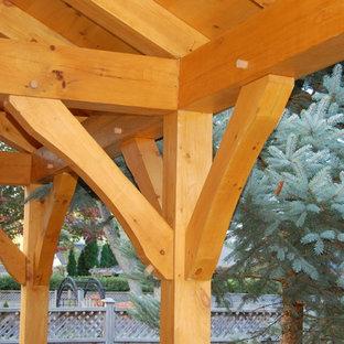 Immagine di un patio o portico american style di medie dimensioni e dietro casa con un focolare, pavimentazioni in cemento e un gazebo o capanno