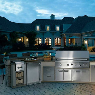Large elegant backyard brick patio kitchen photo in Other with no cover