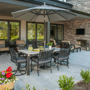 Inspiration for a mid-sized contemporary backyard concrete patio remodel in Seattle with a fire pit and a roof extension