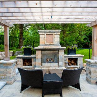 Ejemplo de patio tradicional, grande, en patio trasero, con pérgola, brasero y adoquines de hormigón