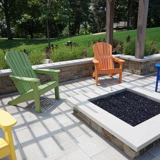 Idee per un grande patio o portico classico dietro casa con pavimentazioni in cemento, un focolare e una pergola