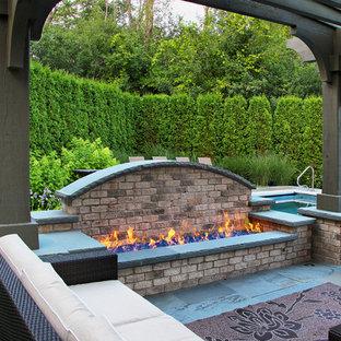 Réalisation d'une terrasse arrière tradition avec un foyer extérieur, des pavés en pierre naturelle et une pergola.