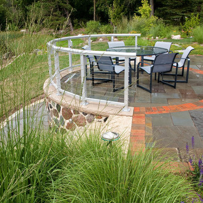 Example of a mid-sized trendy backyard stone patio design in Milwaukee