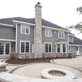 Ispirazione per un grande patio o portico chic dietro casa con un focolare, nessuna copertura e pavimentazioni in mattoni
