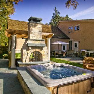 Immagine di un patio o portico eclettico dietro casa con pavimentazioni in pietra naturale, nessuna copertura e un focolare