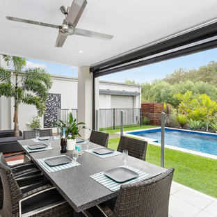 This is an example of a contemporary patio in Gold Coast - Tweed with a roof extension.