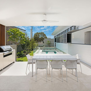 Beach style backyard patio in Sunshine Coast with an outdoor kitchen and a roof extension.