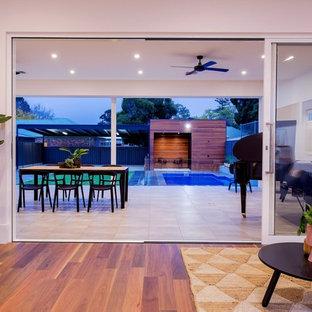 Idee per un grande patio o portico contemporaneo dietro casa con pavimentazioni in pietra naturale e un tetto a sbalzo