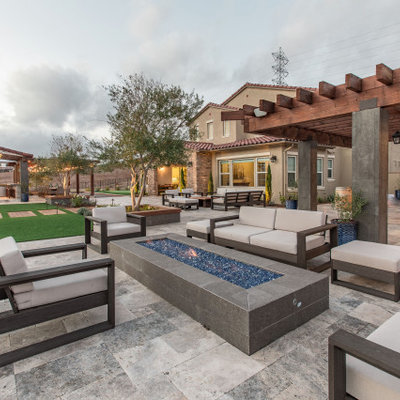 Large trendy backyard stone patio photo in San Diego with a fire pit and a pergola