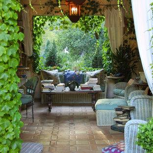 Patio - large mediterranean backyard tile patio idea in Santa Barbara with a roof extension
