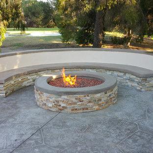 Foto di un patio o portico minimalista di medie dimensioni e dietro casa con un focolare, nessuna copertura e cemento stampato