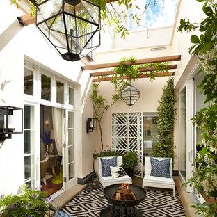 Неиссякаемый источник вдохновения для домашнего уюта: дворик на внутреннем дворе в средиземноморском стиле с местом для костра без защиты от солнца