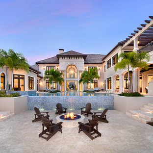 Inspiration for an expansive mediterranean backyard patio in Miami with natural stone pavers, a fire feature and no cover.
