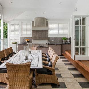 Aménagement d'une terrasse avec une cuisine extérieure bord de mer avec du carrelage et une extension de toiture.