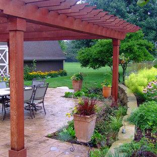 Foto di un patio o portico tradizionale di medie dimensioni e dietro casa con cemento stampato e una pergola