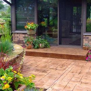Ispirazione per un patio o portico tradizionale di medie dimensioni e dietro casa con cemento stampato e una pergola