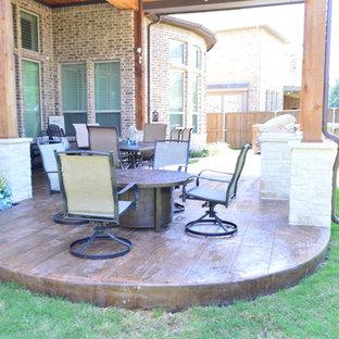 Foto di un grande patio o portico boho chic dietro casa con cemento stampato e un tetto a sbalzo