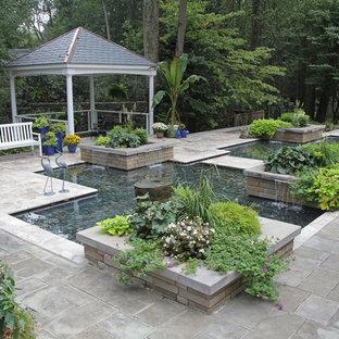Ispirazione per un patio o portico chic di medie dimensioni e dietro casa con una pergola e pavimentazioni in pietra naturale
