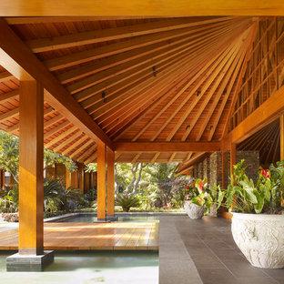 Idee per un patio o portico tropicale con un tetto a sbalzo