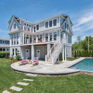 Immagine di un patio o portico stile marinaro di medie dimensioni e dietro casa con fontane, pavimentazioni in pietra naturale e un tetto a sbalzo
